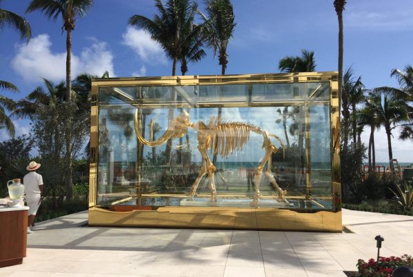 """Gilded woolly mammoth encased in glass vitrine"""
