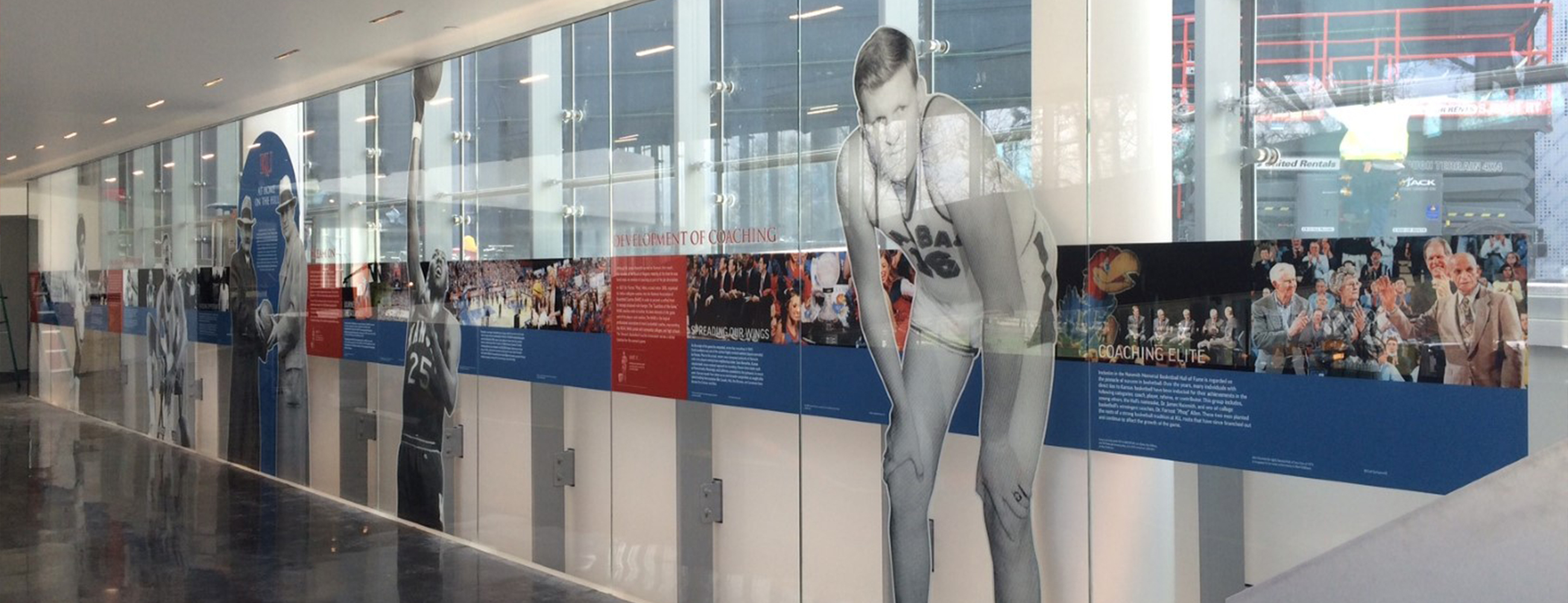 Inside Kansas University, a view of the glass mural depicting images and copy from the history of basketball.