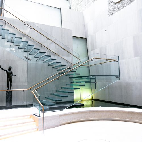 Side view of the all-glass staircase at the Onassis Cultural Center showcasing the stairs, ballustrades and railing.