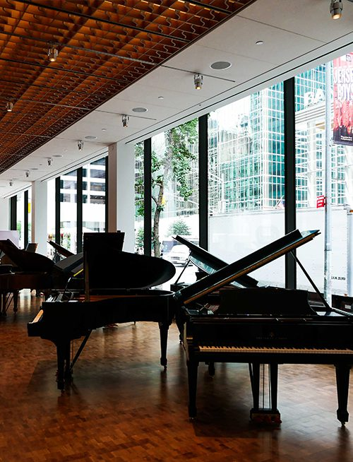 Inside Steinway & Sons looking at grand pianos and insulated glass units consisting of low-iron and low-e glass