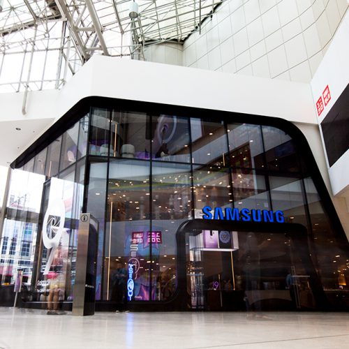 Interior mall view of all-glass façade for Samsung consists of oversized/jumbo, insulated, Low-E, glass units with complex, compound curves fabricated by AGNORA